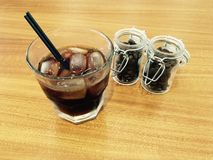 Glass cup with cold coffee drink with ice and black sorbet on a wooden table decorated. With two glass jars with grains inside Stock Images