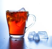 A glass cup with cold tea and ice cubes in it. White-blue background. High contrast. A glass cup with cold tea and ice cubes in it. Close-up. White-blue royalty free stock images