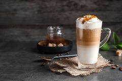 Glass cup with delicious caramel frappe. On table Stock Photos