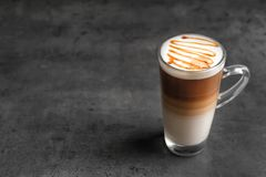 Glass cup with delicious caramel latte. On grey background Royalty Free Stock Photography