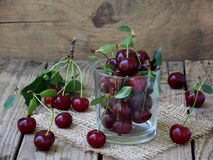 Glass cup filled with cherries. On a wooden background royalty free stock photos
