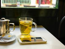 Glass Cup with Freshly Brewed Steaming Hot Green Tea with Pot Honey Smartphone on Table by Window in Cafe. Wooden Chair Tranquil Romantic Cozy Atmosphere Stock Photo
