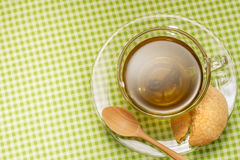 Glass cup of green tea with cookie on green fabric table. Stock Photography