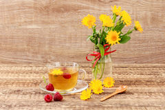 Glass cup of green tea with flowers of calendula and fresh raspb. Erries, fresh bouquet of orange calendula in vase. Wooden boards background. Health-giving Stock Photos