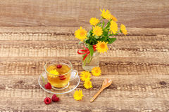 Glass cup of green tea with flowers of calendula and fresh raspb. Erries, fresh bouquet of orange calendula in vase. Wooden boards background. Health-giving Stock Photography