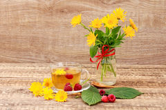 Glass cup of green tea with flowers of calendula and fresh raspb. Erries, fresh bouquet of orange calendula in vase. Wooden boards background. Health-giving Royalty Free Stock Photo