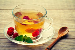 Glass cup of green tea with leaves of mint, fresh raspberries on. A saucer. wooden boards. Health-giving drink Stock Photos