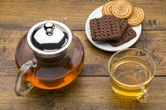 Glass cup of green tea and teapot with various cookies on white plate Stock Image