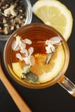 Glass Cup of Herbal Tea with Acacia Flowers and honey on Black Background, top view, Copy space. Health Drink Coldness. Glass Cup of Herbal Tea with Acacia stock photography