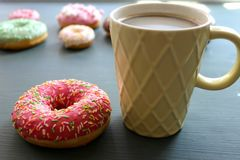 Glass Cup of hot coffee on a black table surrounded by colorful donuts royalty free stock images