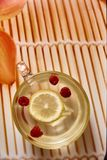 Glass cup with hot ginger tea. With lemon and raspberries royalty free stock photos