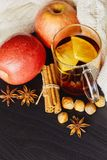 Glass cup of hot spicy drink with apple and orange slices, cinnamon and anise on dark brown background stock photo