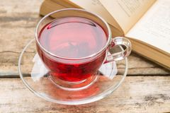 Glass Cup of hot tea with book on old wooden table Stock Photography