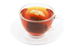 Glass cup of hot tea on plate with tea bag Royalty Free Stock Photo