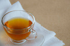 Glass Cup of Hot Tea for Tea Break. Glass cup of tea on white fabric for tea break time Royalty Free Stock Photos