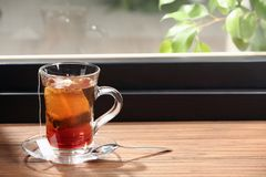Glass cup of hot tea on wooden window sill. Space for text royalty free stock photo
