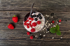 Glass cup with ice cream and ripe berries on a wooden table. Delicious and healthy dessert. Ice cream with currants, strawberries and raspberries. Glass cup with royalty free stock photo