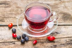 Glass Cup of karkade tea with wild berries on wood background Royalty Free Stock Image