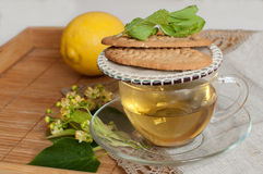 A glass cup of lime flower tea, biscuits and a ripe lemon on a wooden surface Stock Image