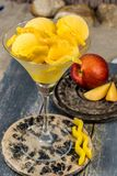 Glass cup with mango peach fruit ice-cream sorbet balls served o. N stone plank on sandy beach royalty free stock images