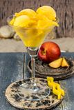 Glass cup with mango peach fruit ice-cream sorbet balls served o. N stone plank on sandy beach royalty free stock image