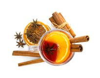 Glass cup of mulled wine, cinnamon and dried orange slices on white background. Top view stock photo