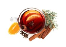 Glass cup of mulled wine, cinnamon, orange and fir branch on white background. Top view stock image