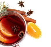 Glass cup of mulled wine, fresh orange and cinnamon sticks. Isolated on white stock images