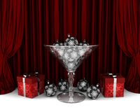 Glass cup with New Year decorations and gifrts. Glass cup with New Year decorations and red gifts in front of the red drapery Stock Image