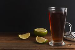 Glass Cup ofblack tea with lime, close up on rustic wooden background. Warm autumn or winter drinks. Isoalted royalty free stock images