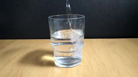 In glass Cup pour water. On black background stock footage