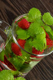 Raspberry Beverage. Glass Cup of Raspberry Beverage with Perfect Fresh Lemon-Balm Leafs on Dark Wooden background Stock Image