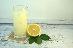 A glass cup with a refreshing juice and ice, on a textile stand and cut half of a lemon with leaves lies on a white wooden table stock photo