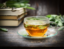 Glass cup with sage tea on rustic table with books, close up Stock Photo