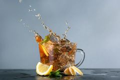 Glass cup and splash of delicious lemon tea with ginger on table against color background stock image