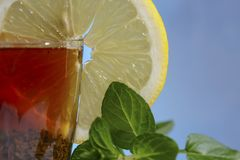 Glass cup of strong black tea on a beautiful blue background with a yellow lemon and green mint. Stock Image