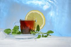 Glass cup of strong black tea on a beautiful blue ice with yellow lemon and green mint. Royalty Free Stock Photos