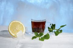 Glass cup of strong black tea on a beautiful blue ice with yellow lemon and green mint. Glass cup of strong black tea on a beautiful blue ice with yellow lemon Royalty Free Stock Photo