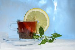 Glass cup of strong black tea on a beautiful blue ice with yellow lemon and green mint. Stock Photography