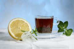 Glass cup of strong black tea on a beautiful blue ice with yellow lemon and green mint. Stock Image