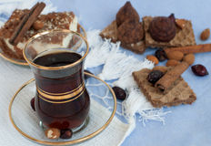 A glass cup of strong black tea, a slice of a pie, cinnamon sticks, wafers and chocolate truffles on a light tablecloth Royalty Free Stock Image
