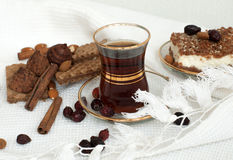 A glass cup of strong black tea, a slice of a pie, cinnamon sticks, wafers and chocolate truffles on a white tablecloth Stock Image