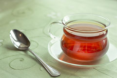 Glass cup of tea. On the green table-cloth Stock Photography