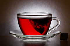 Glass cup with tea bag. Tea bag in a glass cup with a saucer on a table Royalty Free Stock Photo