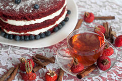 A glass cup of tea and a beautiful homemade cake on a lace surface decorated with blueberries, hips and cinnamon sticks Royalty Free Stock Photo