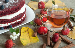 A  glass cup of tea and a beautiful homemade cake on a linen surface decorated with blueberries, hips, lace and cinnamon sticks Stock Photo