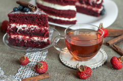 A  glass cup of tea and a beautiful homemade cake on a linen surface decorated with blueberries, hips, lace and cinnamon sticks Stock Image