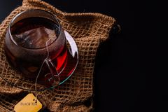 Cup of tea on a black background. A glass cup of tea on the black background and a sackloth stock photos