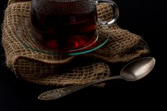 Cup of tea on a black background. A glass cup of tea on the black background and a sackloth royalty free stock image