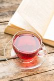 Glass cup of tea with book on table. Reading background Royalty Free Stock Image